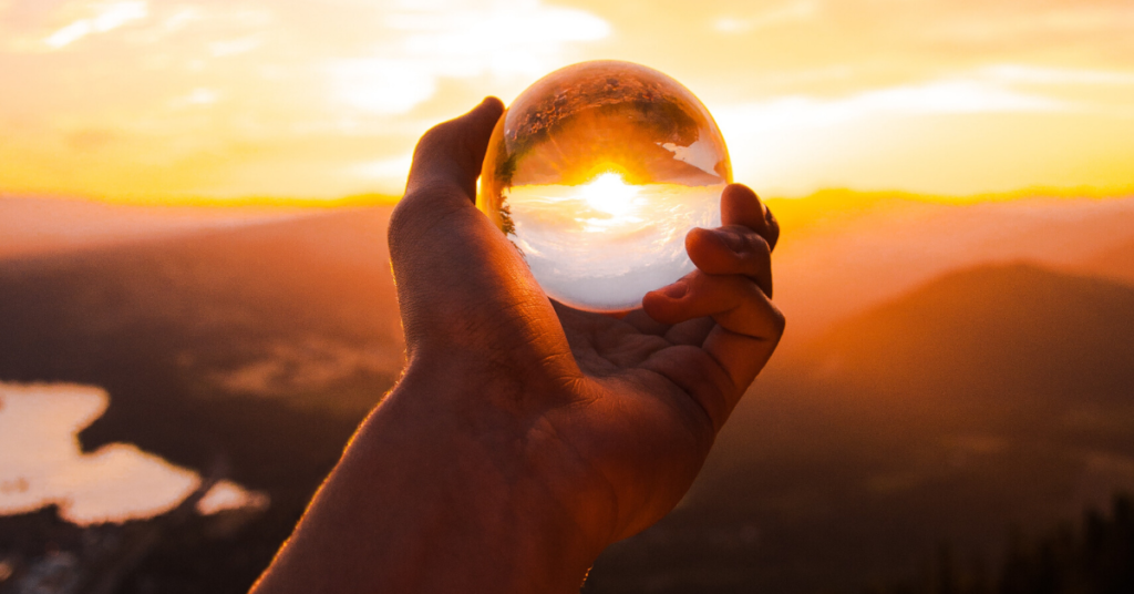man holding crystal ball during sunset