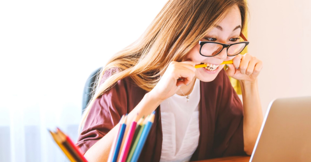 woman biting pencil looking at computer frustrated