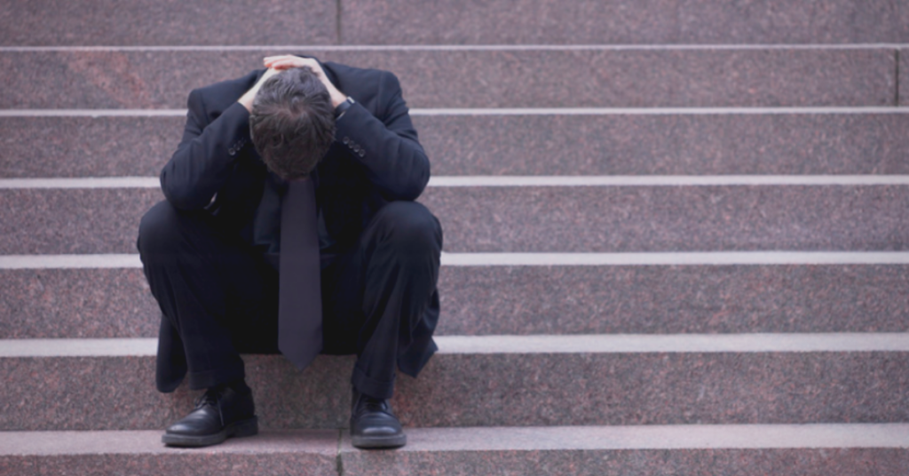 unemployed man sitting on stairs